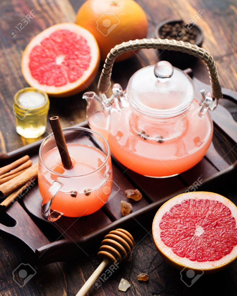 Grapefruit herbal tea with spices and honey in a glass teapot and cup on a dark wooden background