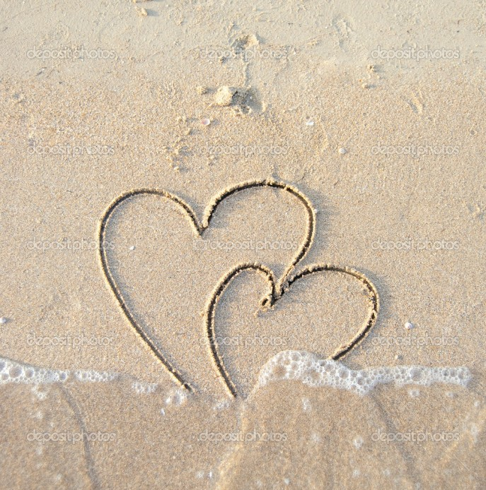 Two connected hearts drawn on wet sand